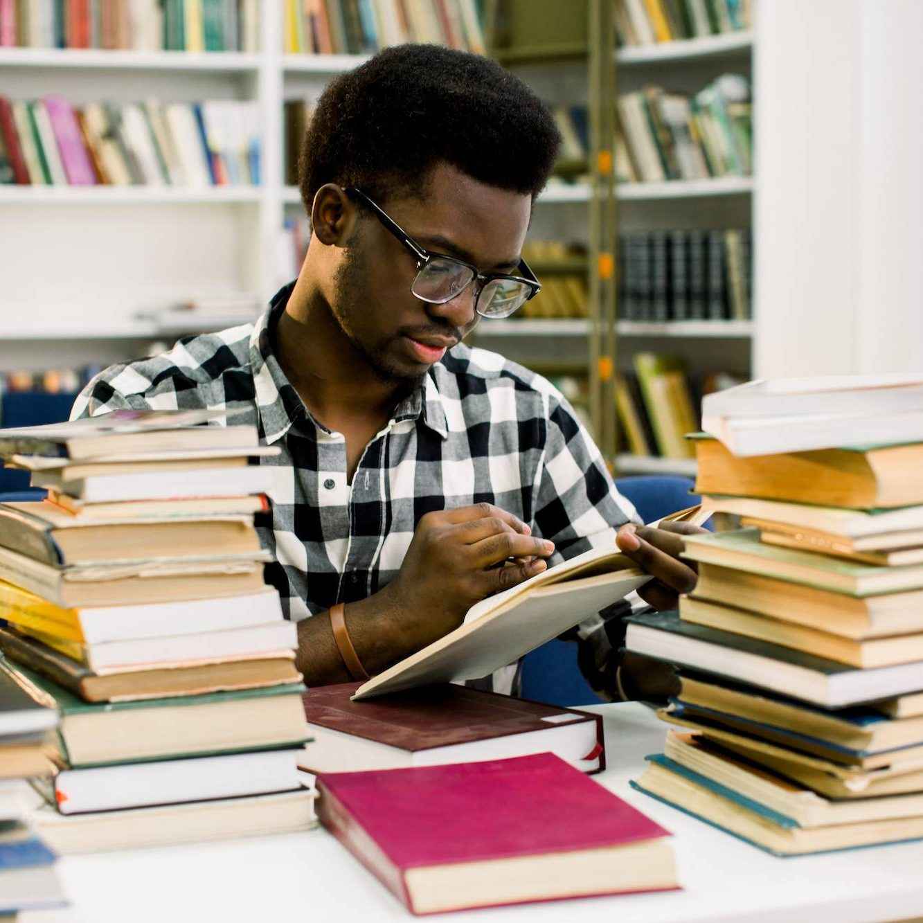 african american male college student sitting at desk in library and reading book. Reflections of paperwork on eyeglasses. Horizontal shape, front view